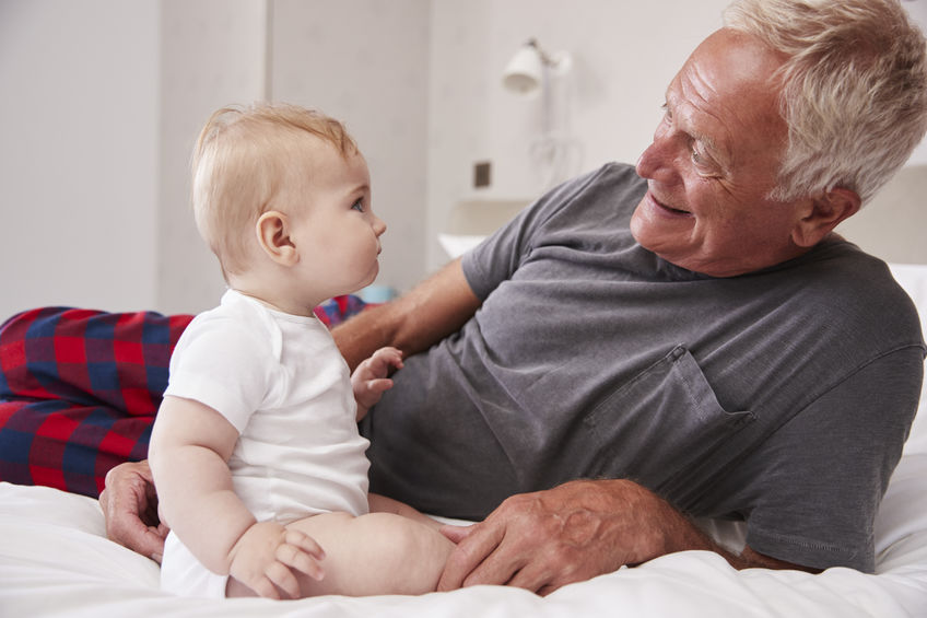 Grandfather Lying In Bed At Home Looking After Baby Grandson